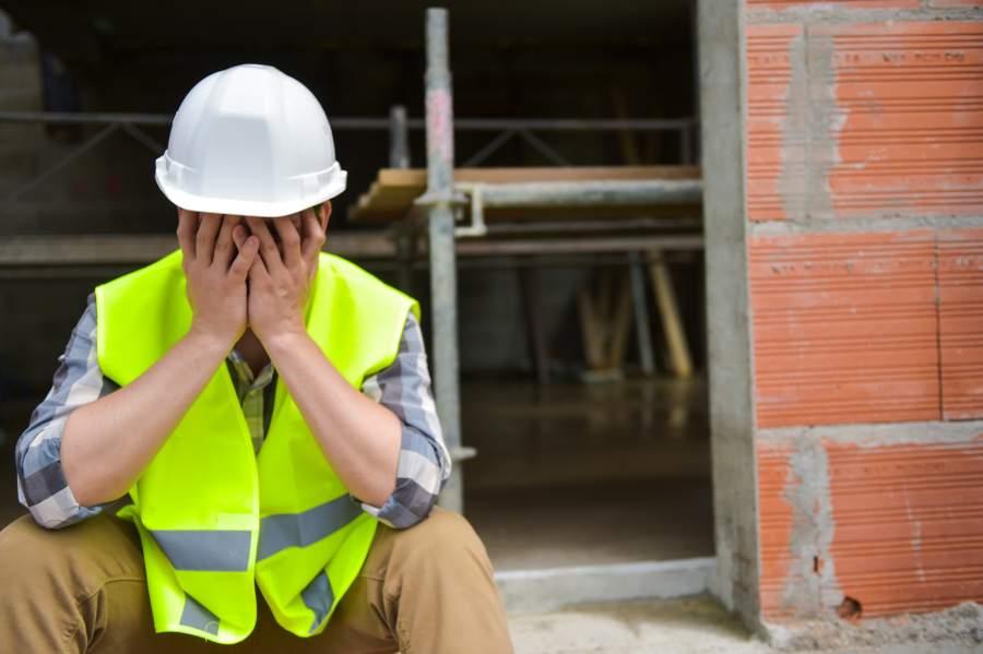 Frustrado trabajador cansado con casco de seguridad blanco y chaleco de seguridad golpea sus manos frente a la cara