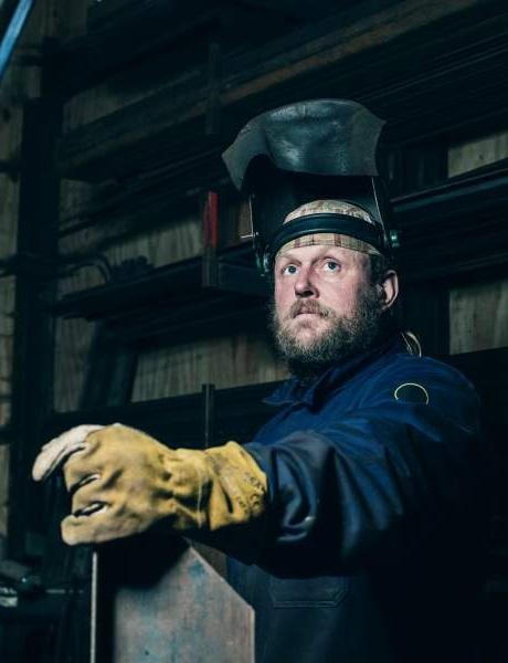 El soldador con equipo de protección personal con visera de casco abierto y guantes mira hacia arriba en el edificio de la fábrica