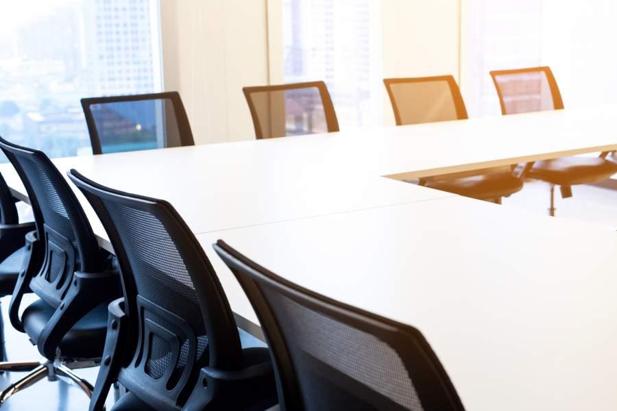 Algunas sillas cómodas vacías con respaldos negros en las mesas blancas en la esquina de la formación del taller para las rondas abiertas de discusión.
