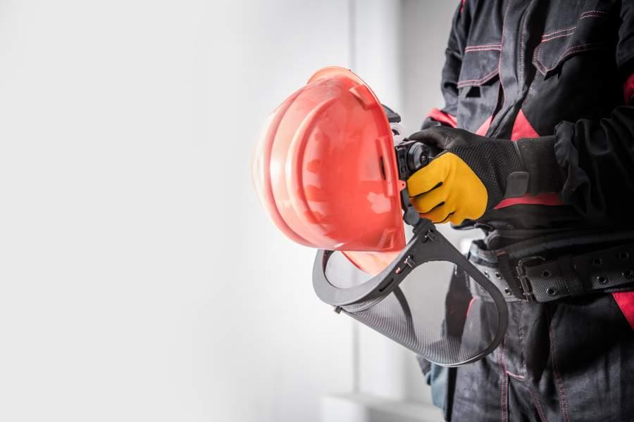 El empleado con ropa de trabajo y guantes de seguridad sostiene un casco de protección naranja con visera en las manos.