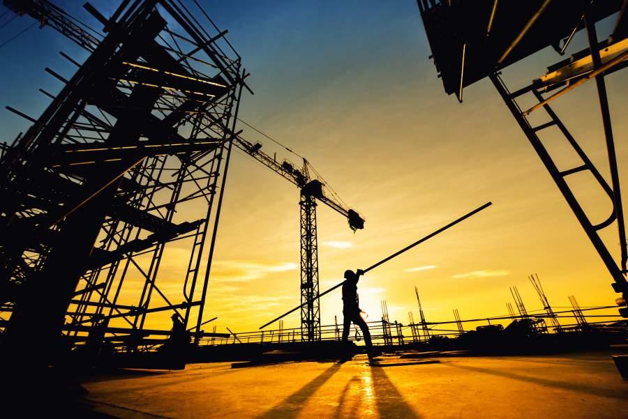 La silueta de un empleado que lleva una larga barra de hierro sobre su hombro sobre la obra, con la puesta de sol en el fondo.