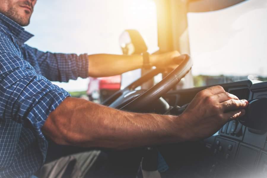 Un hombre con camisa a cuadros conduce un automóvil y mira el tablero en lugar de concentrarse en la carretera.